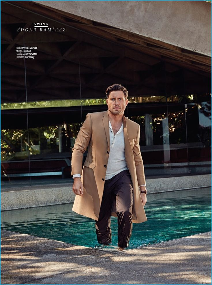 Appearing in a feature for GQ Latin America, Edgar Ramirez dons a single-breasted Topman coat with a John Varvatos henley and pleated Burberry trousers.