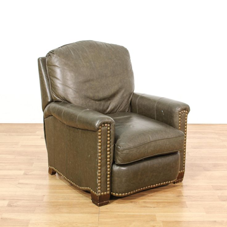 This recliner chair is upholstered in a durable faux leather with a glossy distressed dark brown finish. This armchair has brass studded nailhead trim, carved wood feet and a reclining back with a lift up footrest. Great for lounging in a man cave! #americantraditional #chairs #recliner #sandiegovintage #vintagefurniture