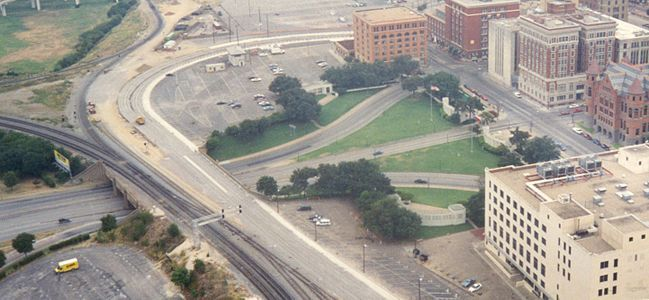 """A view of Dealey Plaza from the mid-1990s. Shown are the Texas School Book Depository and the """"grassy knoll"""" in the upper center, the seven-story Dal-Tex Building. This photo also includes the Art Deco Terminal Annex Federal Building in the lower-right foreground, the former Dallas County Courthouse made of red sandstone, and the Dallas County Criminal Courts Building, adjacent to the Dallas County Records Building."""