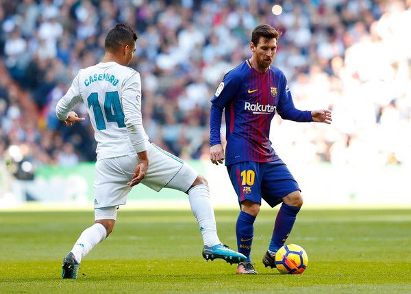 Lionel Messi of Barcelona is challenged by Casemiro of Real Madrid during the La Liga match between Real Madrid and Barcelona at Estadio Santiago Bernabeu on December 23, 2017 in Madrid, Spain.