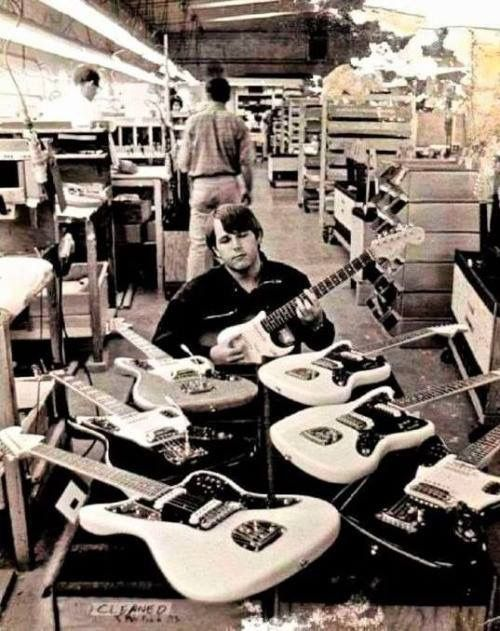 Carl Wilson of The Beach Boys testing guitars at the Fender factory in Fullerton, California 1964