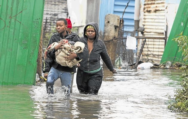 Soweto, ECape Floods | Neighbours help Thembakazi Vanqase, right, to salvage clothes from her flooded shack in an informal settlement near Kliptown, Soweto. | Photo James Oatway / www.timeslive.co.za