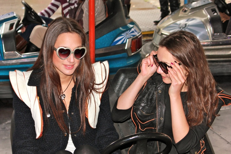 Two adorable sisters having a great time on the bumper cars in Vienna, Austria... both are wearing MRJ Hands-Free Bags.