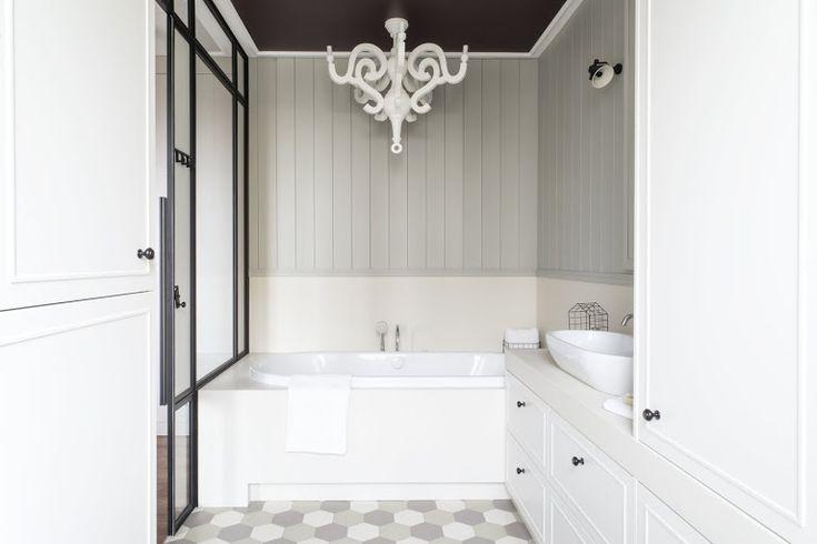 Łazienka prywatna w mokotowskim mieszkaniu, szklana ściana oddzielająca sypialnię, miętowa boazeria, wzór z heksagonalnych płytek. Projekt: Borysewicz i Munzar