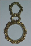 """Pinchbeck quizzing glass of elaborate flourish design. The flourishes of the lens surround are cut upon a fine criss-crossed ground and culminate in a tiny flower at the bottom of the lens. An inner ring of twisted rope design holds the glass. The rigid handle echoes the decoration of the lens surround. Circular maginifying lens with beveled edge. 2 ½"""" long. c 1790."""