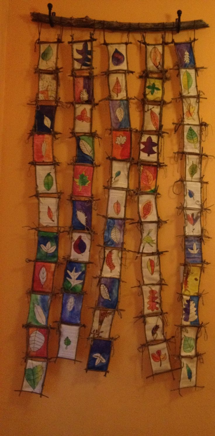 Watercolor leaf paintings on book pages, hung using branches, sticks, and yarn.