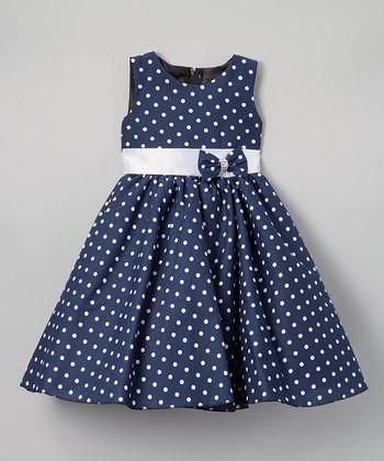 Playful polka dots cover this sleeveless dress that's adorned with a sweet polka dot bow on the front and a ribbon self-tie belt in the back.