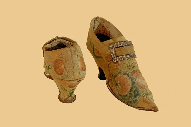 Lady's shoe, 1720-1730, white and yellow emrboidered soft suede, colorful silk thread, brown leather insole, brown roughened leather sole. The two row buckle is set with brilliant cut glass stones with a copper insert. Floral embroidery in interlocking style stitch of pomegranates and blue calyx flowers. Brown roughened non slip sole. Restored 2003. Museum Weißenfels - Schloss Neu-Augustusburg