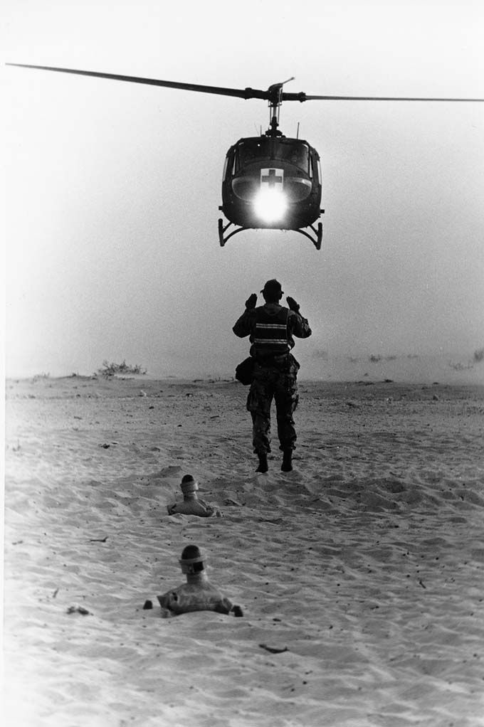 "Soldier directing the landing of a UH-1V Iroquois (""Huey"") helicopter ambulance Operation Desert Shield and Desert Storm"