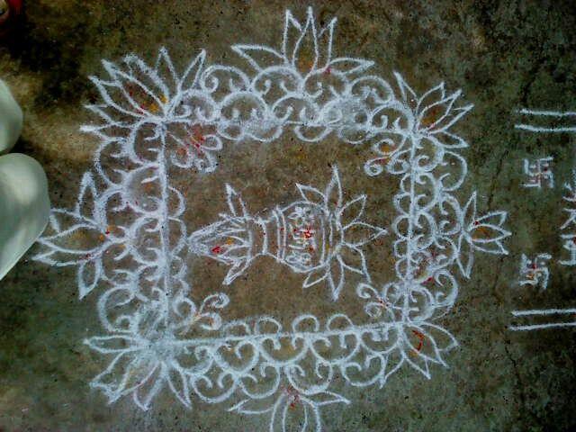Rangoli of a Kalash (Pot) inside a square framed with floral design.