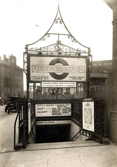 """The stairway at King's Cross in 1925. The sign above the stairs bears the name of the company that built and operated this tube line, the City and South London Railway. In 1890 this  privately-funded venture became the first deep-level underground """"tube"""" railway in the world and the first major railway to use electric traction. When it appeared it would struggle to ensure a return to shareholders, it merged with competitors."""