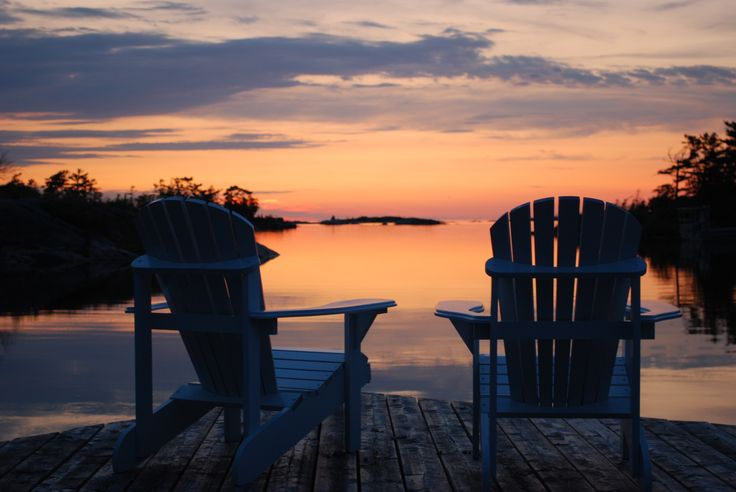 A beautiful sunset over classic Muskoka chairs on a dock. Life is good.