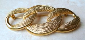 A vintage,  large golden interlocking triple oval brooch by Napier. The brooch design features three polished and textured gold tone interlocking ovals