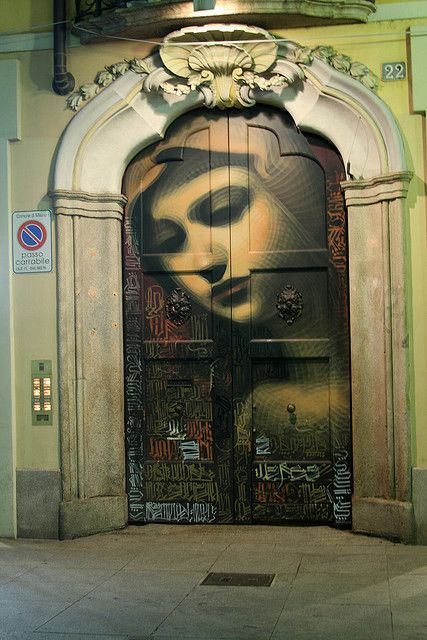 By El Mac (face) and RETNA (calligraphy), stunning street art on an Milan, Italy entryway.