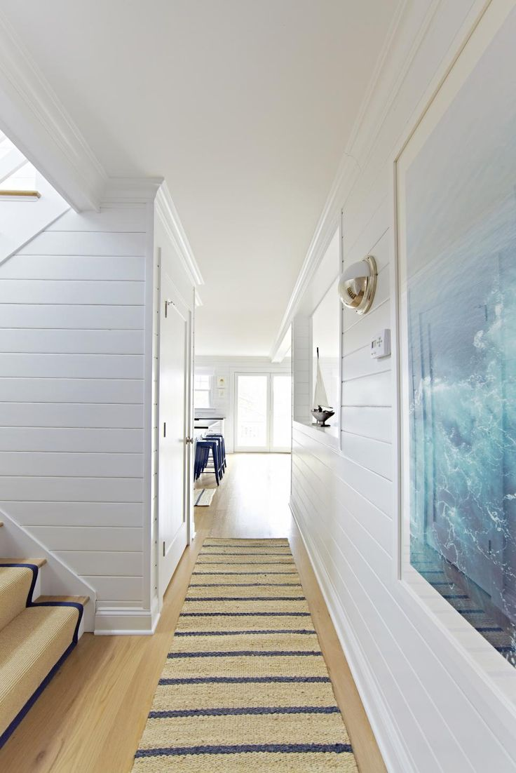 This coastal white bungalow has a light, airy feel. It has a nautical theme with…