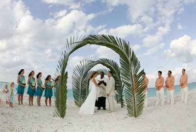 Palm arch lends tropical feel to this #beach wedding