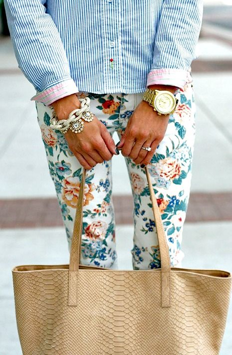 light colored spring outfit with floral print pants, blue striped button up with pink cuffs, and a beige snakeskin bag