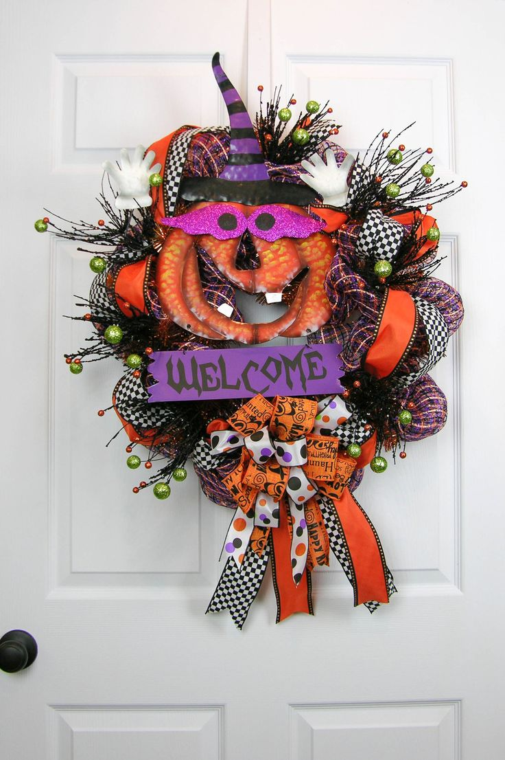 Welcome your guests with this happy Jack-o-Lantern deco mesh wreath. Plaid multi-colored deco mesh with loops of orange and black ribbon, black check ribbon, glittered picks and tied with patterned bo
