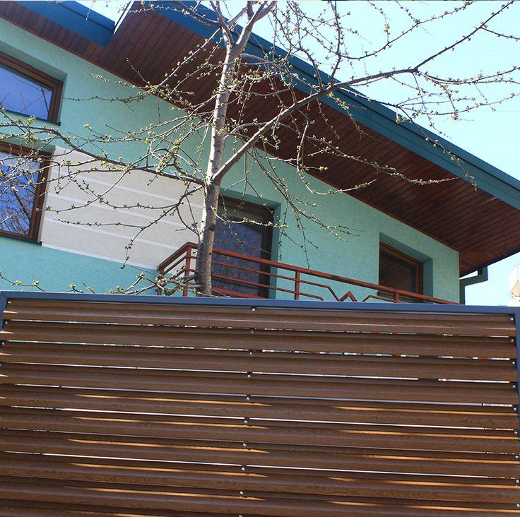 Gard metalic din panou lamelar de culoare maro.