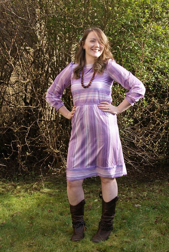 A lovely Vintage 70s Disco Dress! In a beautiful shimmery striped purple, blue and lilac shades fabric, this dress is perfect either dressed down with boots or up with heels! Has long sleeves and an elasticated waist with a knee length skirt. Zips up back. In good vintage condition.