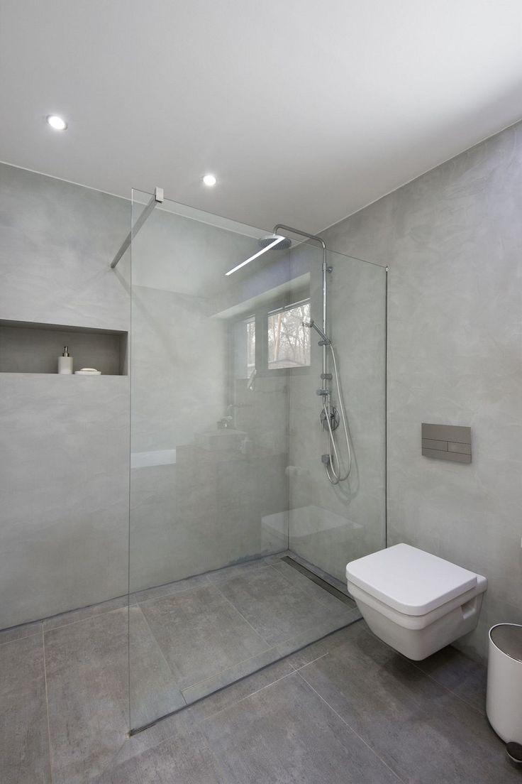 Sprchový kout má skleněnou zástěnu a odtok v podlaze. Na stěnách je Pandomo stěrka.