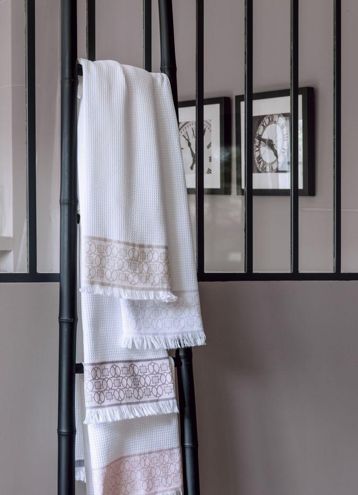 Serviettes de bain Le Jacquard Français en nid d'abeilles blanc avec liteau coloré motif art déco beige, bleu gris violet ou rose. modèle Esthète. 100% micro coton ultra doux. Existe en Serviettes invité et de toilette, drap de douche et de bain. Photographiés dans une salle de bain avec verrière et porte-serviette en bambou noir.