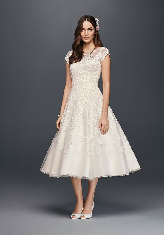 Lace tea-length dress with illusion neckline, cap sleeves, and beaded lace appliqués.