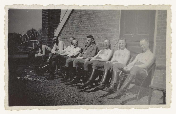Anonymous | Leden van de WA, Anonymous, 1943 | Leden van (vermoedelijk) de WA, de Weerafdeling van de NSB, zitten, deels met bloot bovenlijf, in de zon voor een gebouw. Allen dragen hoge zwarte laarzen.