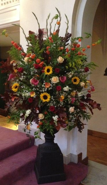 Autumnal urn arrangement of red gladioli, delphinium, red and green oak leaves, physalis, red Naomi, peach avalanche and candle light roses, sun flowers, cream stocks, tanacetum, red and orange calla lily, leucadendron.