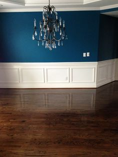 Sherwin Williams Oceanside blue walls; Dining room with dark hardwood floors; Crystal and iron chandelier; 2nd step to the transformation was restaining the floors