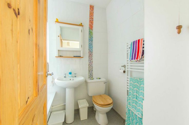 Small but perfectly formed! I kept my bathroom suite and tiles white, and made the multicoloured fuzed glass tiles to go the full hight of the room from behind the toilet, bringing a art focal point to the room, as it's the main colour it stands out and shines. I choose different colour towels and candles to draw out single colours from the glass tiles.