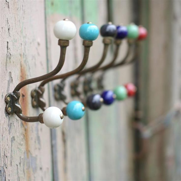 A classically styled sturdy metal double coat hook finished with colourful  ceramic knobs. These practical hooks look great singly or arranged in a row.