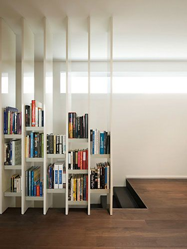 nice way to do a room divider, shelves only as high up as you can reach so the room still feels open