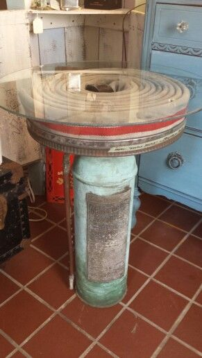 Repurposed fire hose and extinguisher turned side table. Available at domestic  possession  In madison ct or on our facebook page 2 gal salvage