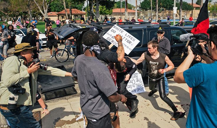 In this scene from the scuffle, counter protesters appear to fight with a KKK member as he stabs an attacking protester. Blood splatters can be seen on the pavement