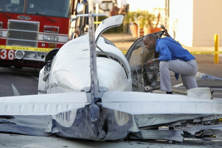 An aviation safety inspector looks inside the cockpit of a small plane after it crashed in a shopping centre parking lot in San Diego. One woman was killed and another seriously injured, a fire spokesman said.
