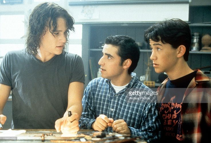 Heath Ledger, David Krumholtz, and Joseph Gordon-Levitt standing at table in a scene from the film '10 Things I Hate About You', 1999.