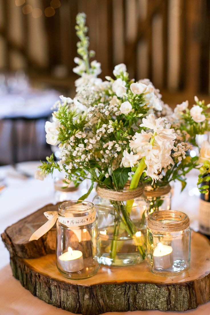 Slice of wood, tea light candles in jars, tied with ribbon or twine, mason jars with flowers