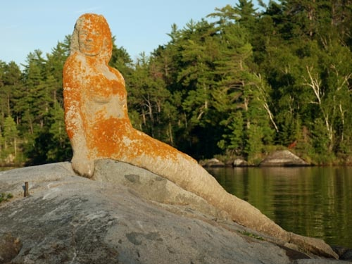 Mermaid.  The myth has it that a young woman drowned near this rock, so her father constructed a mermaid in her memory. Rainy Lake, Fort Frances. Ontario, Canada.