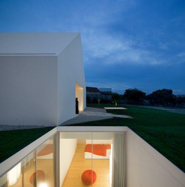 Localizada em Leiria, Portugal, esta casa subterrânea é dividida em área íntima, com pátios privados, e espaço social, ao redor de uma abertura que recebe luz natural.