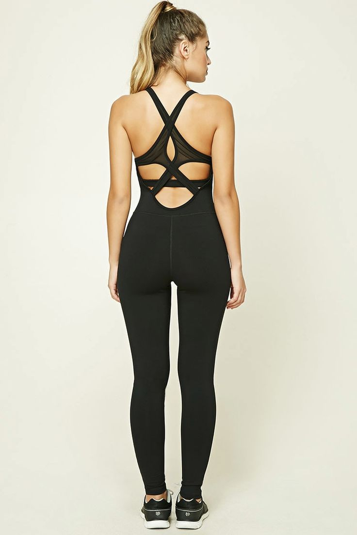 A stretch knit athletic jumpsuit featuring a sleeveless cut, mesh-paneled straps that cross in back, a sports bra layer with removable cups, and moisture management.