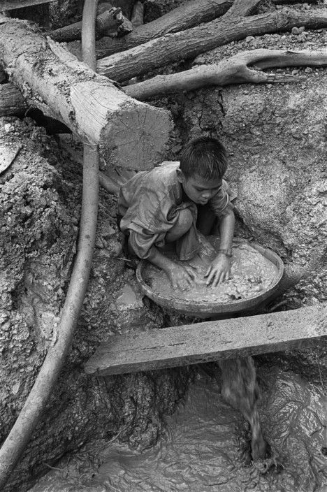 John Vink  CAMBODIA. Pailin. 7/04/2002: Gem miner sifting ore to find ruby and sapphire.