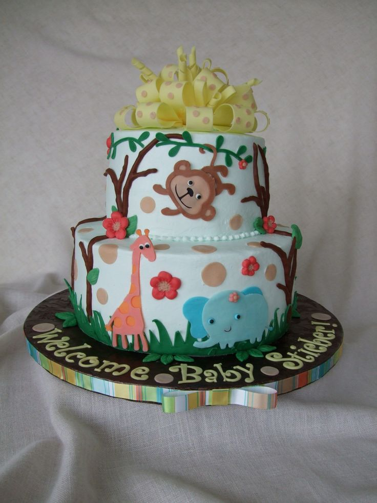 Baby shower jungle theme cake - 7 and 10 inch buttercream chocolate cake.  Fondant bow and letters. Everything else is modeling chocolate cut with my Cricut Cake. TFL.