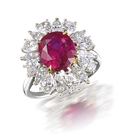 A ruby and diamond ring, by Harry Winston The oval mixed-cut ruby, weighing 3.61 carats, within a surround of marquise and pear-shaped diamonds, mounted in platinum and 18k gold, diamonds approximately 1.75 carats total, signed Winston.