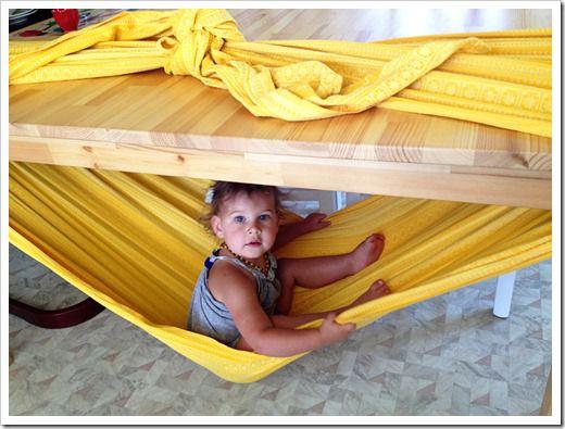 Hamaca improvisada con una tela larga o sábana atada a una mesa - 32 Trucos para padres que te harán la vida más fácil