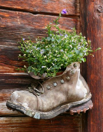 I love this idea to hang an old work boot planter on a fence!