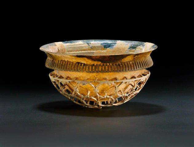 A Roman iridescent colourless glass cage cup, the Constable-Maxwell Cage-Cup, circa A.D. 300 ; blown or cast in colourless glass, wheel-cut, ground and polished, the hemispherical body with a rounded base and curved, out-splayed rim, the decoration comprises a faint horizontal ridge below the rim and above a collar consisting of a projecting openwork flange with 103 perforations separated by darts