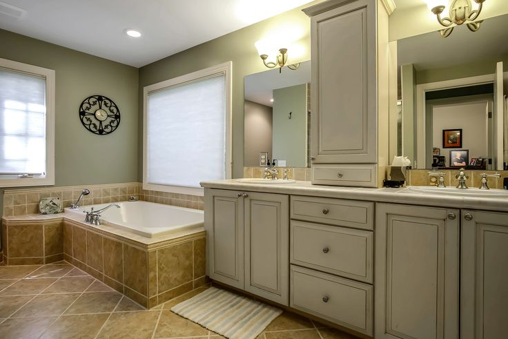 Mellow bathroom: light green paint and rustic white cabinetry #Michigan #RealEstate