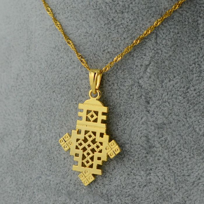 This petite and bold Axum cross is perfect for everyday wear. This style of necklace is one that can almost never be found anywhere but in Ethiopia.The city of Axum is located in northern Ethiopia and is apart of the Tigray region. The city was also the capital of the Axumite Empire and it was this empire that established its Orthodox Christian roots in Ethiopia making it one of the first countries to adopt Christianity under King Ezana's rule in 341 ADThis pennant is 18K go...