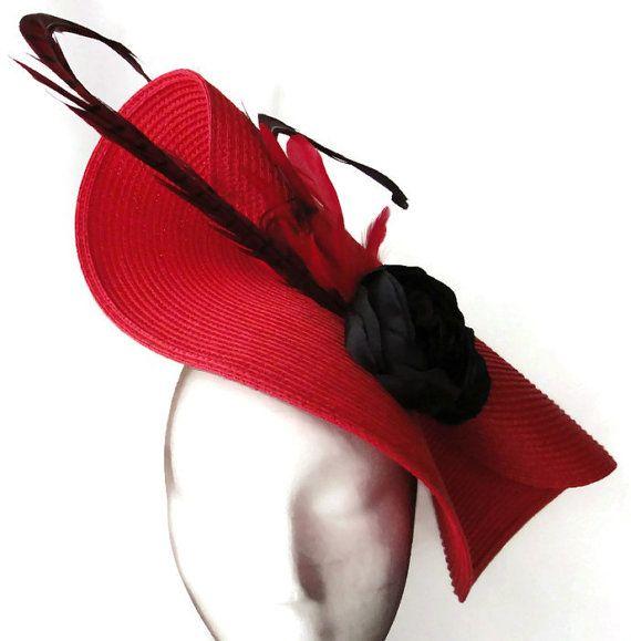 Tocado rojo y negro. El tocado tiene una base roja acompañada con flor negra hecha a mano y plumas de faisan de color rojo y negro. Es un tocado de boda